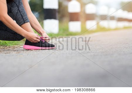 sport fitness people and lifestyle concept - close up of woman tying shoelaces outdoors