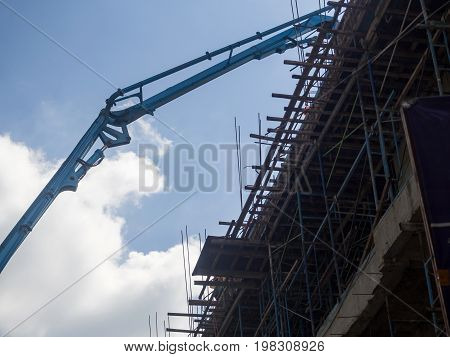 Building Under Construction. The Site With Cranes Against Blue Sky