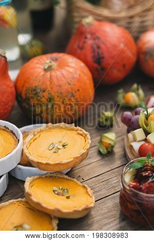 Beautiful pumpkin pies lying next to pumpkins, dried tomatoes and physalis on a wooden table
