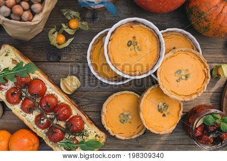 Pie with cherry tomatoes, pumpkin pie, Sun dried tomatoes, Physalis, paper bag with nuts on a wooden table. Top view
