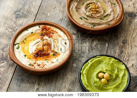 Different hummus bowls. Chickpea hummus, avocado hummus and lentils hummus on wooden table