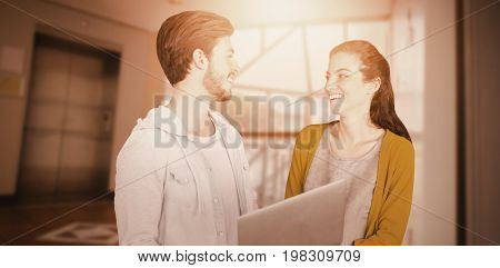 Business colleagues looking at each other while using a laptop against foyer area with elevator