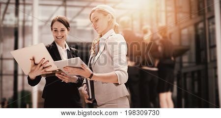 Smiling business women using digital tablet against businesspeople forming huddle in office premises