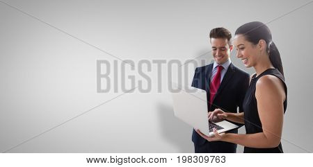 Business colleagues using laptop against grey vignette