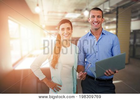 Smiling business people using a laptop against tables in office cafeteria