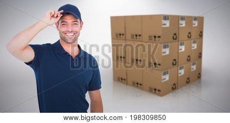Portrait of happy delivery man wearing cap against grey background