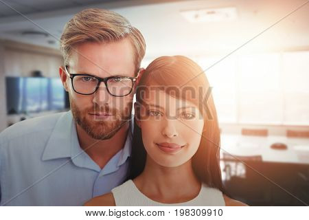 A couple are posing head against head  against empty boardroom in office