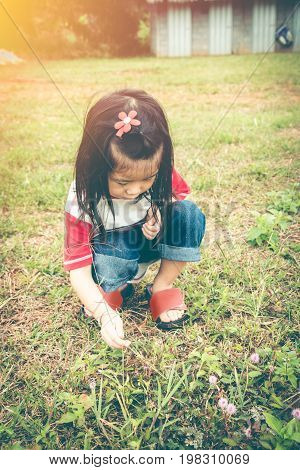 Adorable child exploring nature and the outdoors with sunlight. Asian girl sitting on ground discovering learning new. Education concept. Travel on vacation. Vintage effect style.