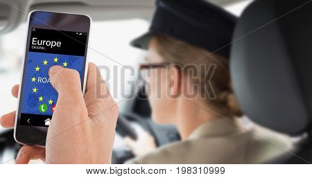 Cropped hand of man using mobile phone against chauffeur looking at the road