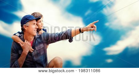 Father pointing away with his son  against blue sky with clouds