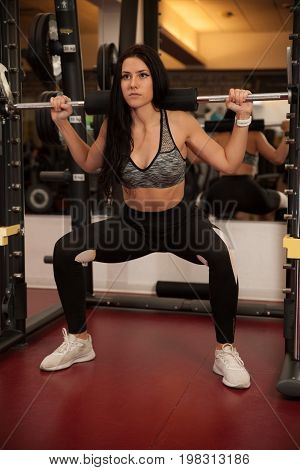 Active Young Woman Doing Squate In Fitness Gym Club
