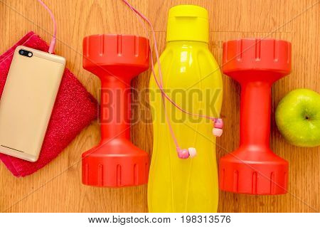 Athlete's set with two pink dumbbells, smarphone with pink headphones, green appple and a yellow bottle of water, in a row on wooden background.