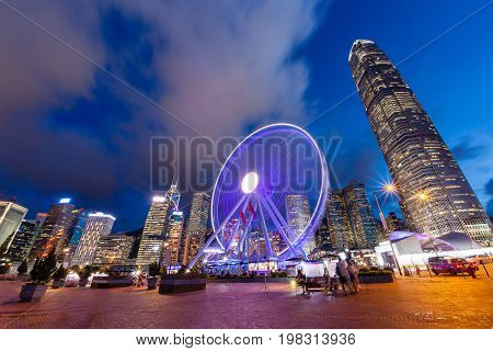 Sunset on Hong Kong's vibrant night life at Central Pier near Victoria Harbour with the Observation Wheel in motion and the downtown financial district in the background.