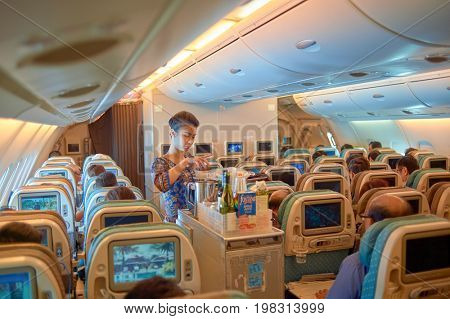 SINGAPORE - NOVEMBER 03, 2015: flight attendant serve food and drinks to passengers on board of Singapore Airlines Airbus A380