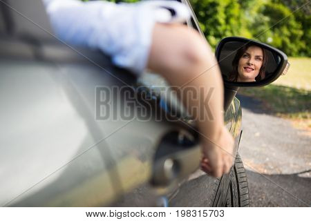 Reflection of happy woman in wing mirror driving a car