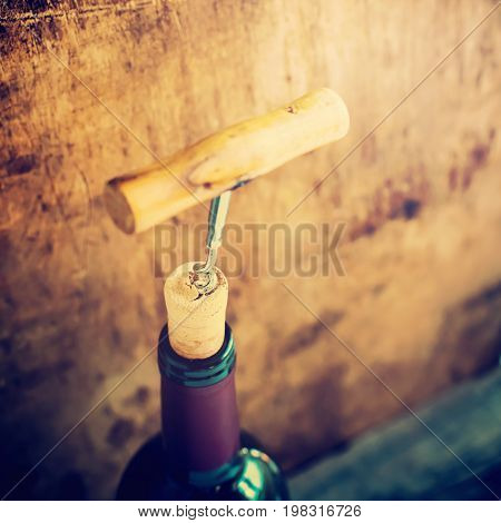Bottle Wine With Corkscrew On Wooden Background