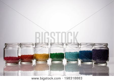 colored rice in glass jars is by colors of the rainbow