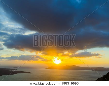 A black cat on a ledge at sunset at Fira town, with view of caldera, volcano, Santorini, Greece. Cloudy dramatic sky.
