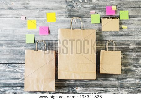 Blank brown paper shopping bags and stickers hanging on wooden wall. Merchandise concept. Mock up