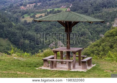 Wooden Seating Bench With Table In Nature Under Wooden Umbrella