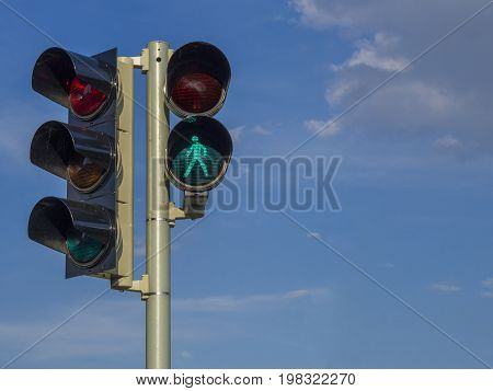 traffic light - semaphore - green walking figure puppet on blue sky background