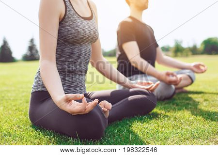Man and woman practice acro yoga in the park meditation