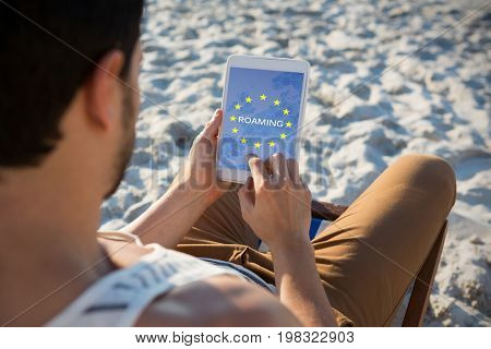 Roaming text on European Union flag against high angle view of man using digital tablet at beach