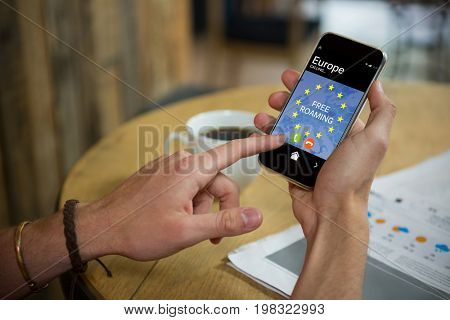 Free roaming text and European Union flag on mobile display against man using mobile phone at table in cafe