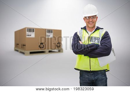Worker wearing hard hat in warehouse against grey background