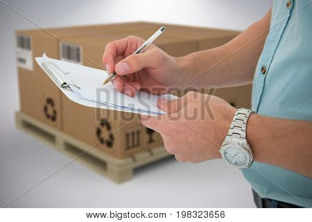 Delivery man writing on clipboard against grey background