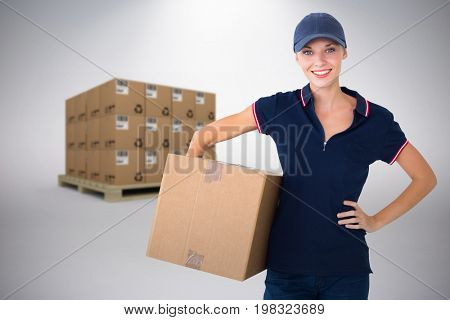 Happy delivery woman holding cardboard box  against grey background