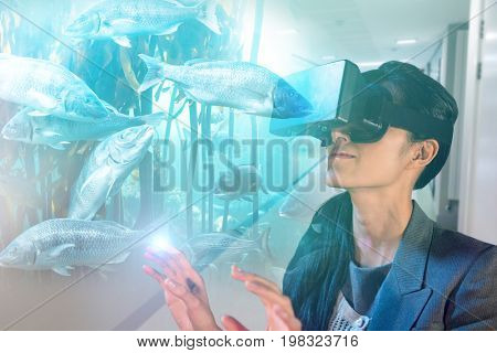 Young woman wearing black virtual reality simulator glasses against big fish swimming in a tank