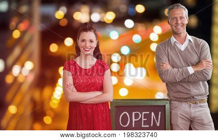 Portrait of coworker with arms crossed standing open sign against glowing road in city at night