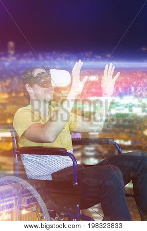 Smiling man using virtual reality glasses while sitting on wheelchair against high angle view of illuminated crowded cityscape