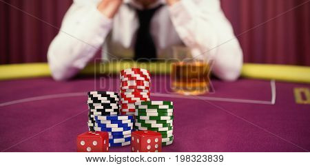 Dice with stack of colorful casino tokens against man betting his house at poker game