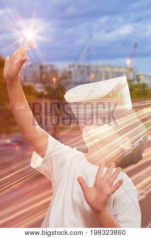 Boy using virtual reality simulator glasses against light trails on city street