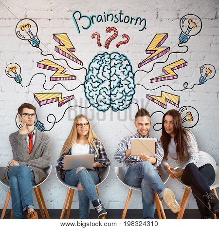 Cheerful young businesspeople sitting on chairs and using laptops ni brick interior with colorful brain sketch on wall. Brainstorm and partnership concept
