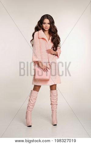 Fashion photo of fashionable woman in pink coat with handbag wears in trendy leather high boots posing isolated on studio background.