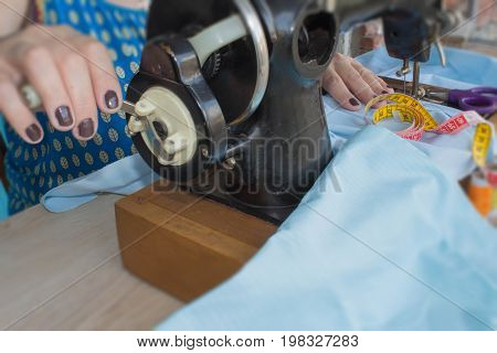 woman seamstress sitting and sews on sewing machine. Dressmaker work on the sewing machine. Tailor making a garment in her workplace. Hobby sewing as a small business concept poster