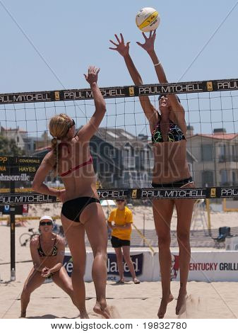 MANHATTAN BEACH, CA. - JULY 18: Chelsea Hayes spike and Jenny Kropp attempting to block at the AVP Manhattan Beach Open on July 18, 2009 in Manhattan Beach, CA.