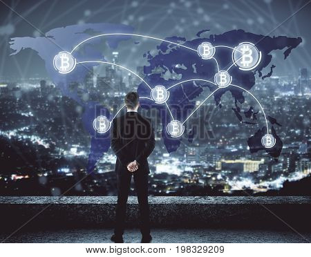 Back view of young businessman standing on rooftop and looking at night city with abstract bitcoin map. Cryptocurrency concept. Double exposure