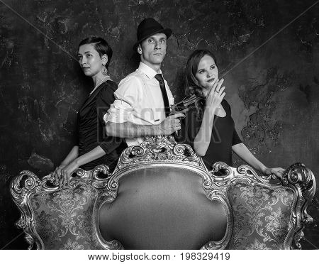 Detective story shooting in studio. Man and two women. Agent 007. A man in a hat with a pistol and two women in black dresses
