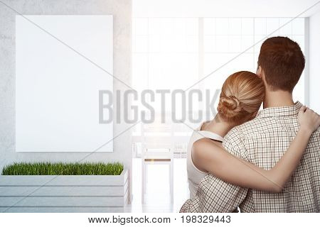 Back view of young couple cuddling in interior with city view blank poster on concrete wall and daylight. Mock up 3D Rendering
