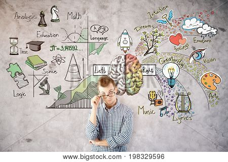 Thinking young man on concrete wall background with abstract brain sketch. Left and right hemispheres concept