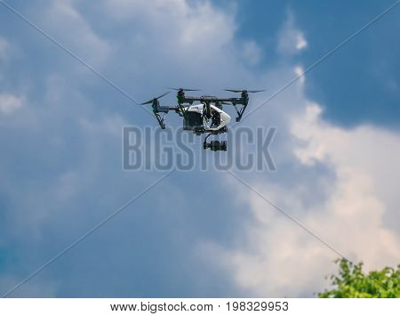 Drone in the blue sky. Quadrocopter hovered in the air.