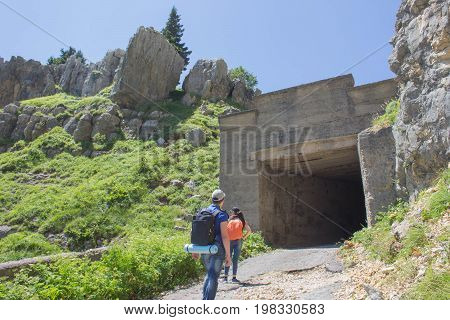 Tourists in the mountains at the artificial tunnel. Travel adventure and hiking activity active and healthy lifestyle on summer vacation and weekend tour