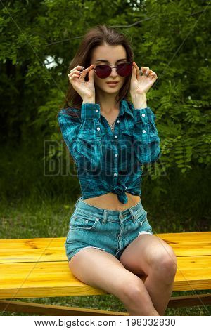 a beautiful young woman in a Plaid Shirt and sunglasses sitting on a bench and posing for the camera