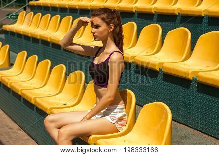 a svelte young fitness woman in a short top and shorts sitting in the stadium