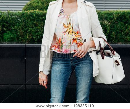 Fashionable and high style expensive female bag. Jeans and fashionable colored blouse. Sales bag fashion concept. Close up of stylish female leather bag outdoors. Part of body. Street style. Outdoor.