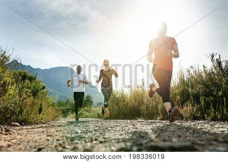 Group Of Friends Cross Country Running Together On A Trail